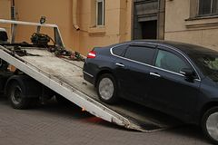 Loading a car onto a tow truck. Loading a wrongly parked black car onto a tow truck stock photography