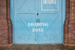 Loading zone painted on the blue wood door stock photo