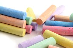 Loads of colored chalks. Loads of brightly colored chalks on a white reflective background Royalty Free Stock Photography