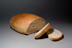 Loaf of bread. With two slices on gray background Stock Images