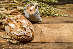 Loaf of bread and a bag with grains Royalty Free Stock Images