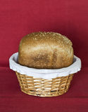 Loaf of Bread in Basket. A loaf of freshly-baked bread sprinkled with some sesame seeds in a small simple round basket against the deep red mat Stock Photo