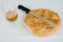 Loaf of bread, beer and knife on white table, food closeup. Top Stock Photography