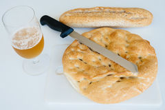 Loaf of bread, beer and knife on white table, food closeup. Top Stock Photo