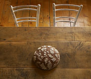 Loaf of bread on brown table. Loaf of bread still life on brown table and two chairs Stock Photo