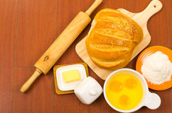 Loaf of bread, cheese, cracked eggs in a bowl and Stock Images