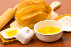 Loaf of bread, cheese, cracked eggs in a bowl and Royalty Free Stock Image