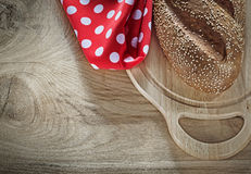 Loaf of bread chopping board tablecloth on wooden background Royalty Free Stock Photos