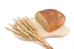 A loaf of bread and ears of corn on a cutting board Royalty Free Stock Images