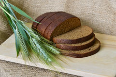Loaf of bread. Loaf of fresh sliced dark bread on a wooden cutting board, jute background Stock Image