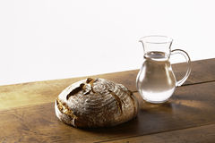 A loaf of bread and a jug of water on table Royalty Free Stock Images