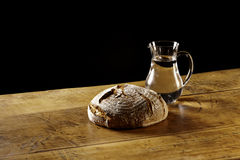 A loaf of bread and a jug of water on wooden table. On black background Royalty Free Stock Photo