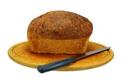 A Loaf of Bread, Knife and a Bread Board Stock Images