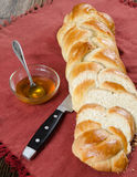 Loaf Bread and Oil. Sliced bread loaf on a red table cloth with a bowl of oil in the back Stock Images