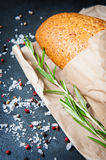 Loaf of bread with rosemary salt and pepper on paper Royalty Free Stock Image