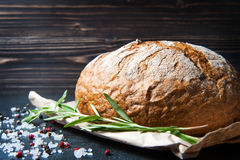 Loaf of bread with rosemary salt and pepper on paper Stock Images