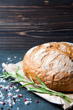 Loaf of bread with rosemary salt and pepper on paper Royalty Free Stock Images