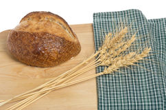 Loaf of bread with sheaf of wheat. A loaf of bread on cutting board with a sheaf of wheat Royalty Free Stock Photo