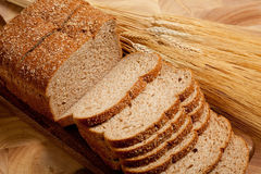 A loaf of bread and shock of wheat on wood Stock Photography