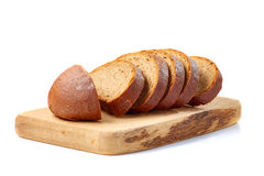Loaf of bread sliced on wooden board ower white. Loaf of bread sliced on wooden board. Isolated on white background royalty free stock image