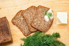 Bread. Tasty, home made, baked, wholegrain, wholemeal, brown bread. with chopped dill, butter and knife on the wooden board. Polis Stock Photography