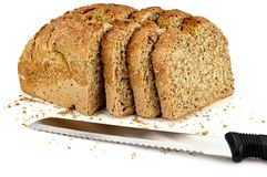 A loaf of bread with a three slices and a knife Stock Photo