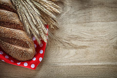 Loaf of bread wheat ears red polka-dot tablecloth on wooden boar Stock Photography