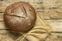 Loaf of bread with wheat grains on wooden background Stock Image