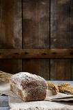 Loaf of Bread with wheat spikelets on a wooden background Royalty Free Stock Image