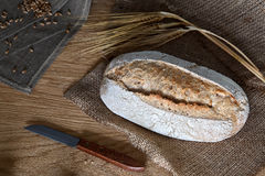 Loaf of bread on a wooden background. A loaf of bread with a knife and some barley ears a wooden background Royalty Free Stock Photo