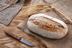 Loaf of bread on a wooden background. A loaf of bread with a knife and some barley ears a wooden background Stock Photography