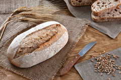 Loaf of bread on a wooden background. A loaf of bread with a knife and some barley ears a wooden background Stock Photo