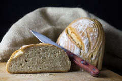 Loaf of bread. On wooden board with a knife Royalty Free Stock Images