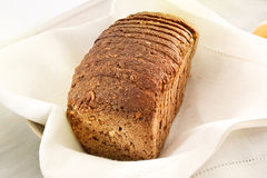 Loaf of brown bread. Loaf slices of brown bread on linen napkin Royalty Free Stock Photography