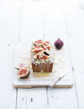 Loaf cake with figs, almond and white chocolate on wooden serving board over grunge background, selective focus. Stock Images