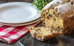 Chocolate Chip Bread. Loaf of chocolate chip bread sliced and sprinkled with confectioner`s sugar on black marble. Two white plates on red checkered napkin Royalty Free Stock Photography