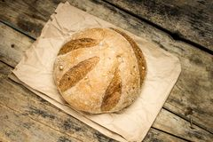 Loaf of fresh baked wheat bread on wood background Royalty Free Stock Photos