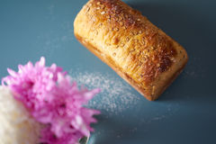 A loaf of fresh bread lying on colored surface Royalty Free Stock Photos