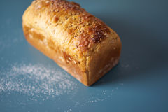 A loaf of fresh bread lying on colored surface Royalty Free Stock Images