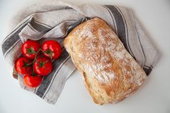 Loaf of fresh bread with tomatoes on the table royalty free stock photo