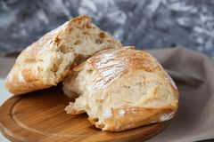 Loaf of fresh bread on wooden board royalty free stock photography