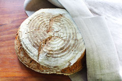 Loaf of fresh spelt flour bread in kitchen towel Stock Photo