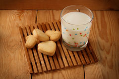 Loaf and glass of milk standing. Buns with sesame seeds and a glass of milk standing on a wooden background Royalty Free Stock Photos