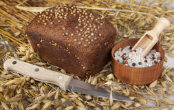 Loaf of homemade bread with black mustard seeds on a table with spikelets of rye oats and salt shaker salt and knife Royalty Free Stock Image
