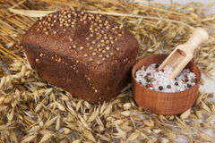 Loaf of homemade bread with black mustard seeds on a table with spikelets of rye and salt shaker of salt Stock Photo