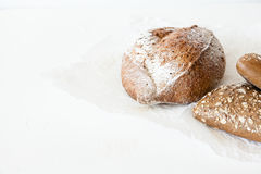 A loaf of homemade bread in a paper on a white background with space for your text. Stock Photo