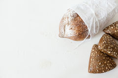 A loaf of homemade bread in a paper on a white background with space for your text. Royalty Free Stock Photography