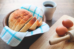 Loaf of homemade bread sliced on wooden bowl on wood table with eggs Royalty Free Stock Image