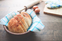 Loaf of homemade bread sliced on wooden bowl on wood table Royalty Free Stock Images