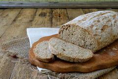 A loaf of homemade bread from whole grain  and rye flour whith sesame seeds on a wooden background. Copy space. Photographing with Stock Photo